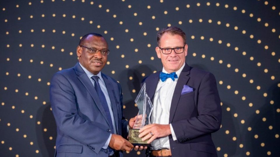 Minister of Infrastructure and Guest of Honor, Amb. Claver Gatete (L) hands over the 2018 RDB Business Excellence Awards Investor of the Year award to I&M Bank Rwanda's MD, Robin Bairstow (R)