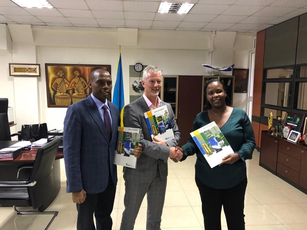 From left to right, RMB CEO, Dr. Francis Gatare, Gasmeth CEO, Stephen Tierney and RDB CEO, Ms. Clare Akamanzi pose with Invest in Rwanda booklets after signing the Methane gas extraction agreement at RDB office