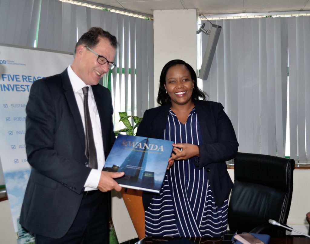 RDB CEO, Clare Akamanzi (R) hands over a book that explains Rwanda's transformational growth story to the German Minister, Gerd Muller (L) today