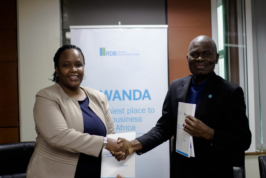 RDB CEO, Clare Akamanzi (L) shakes hands with FAO Representative in Rwanda, Gaulbert Gbehounou (R), after signing the new partnership today at RDB offices